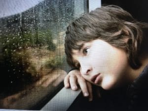 A young person sadly looking out a window while it is raining